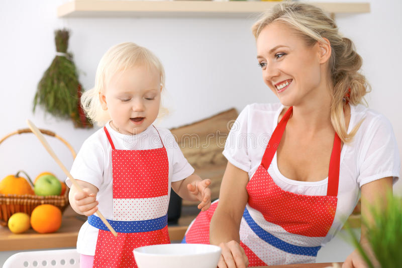 Família feliz na cozinha Filha da mãe e da criança que cozinha o mais breakfest saboroso fotografia de stock