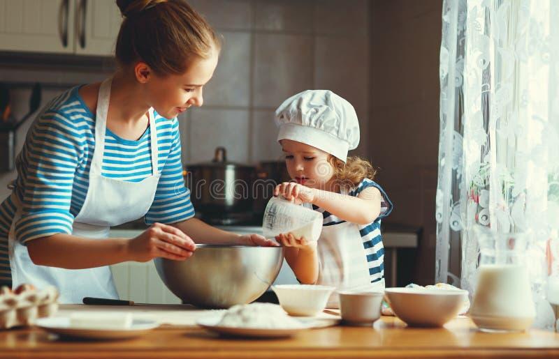 Família feliz na cozinha a mãe e a criança que preparam a massa, cozem fotografia de stock