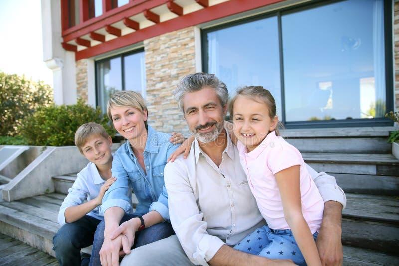 Família feliz na frente de sua casa nova imagens de stock royalty free