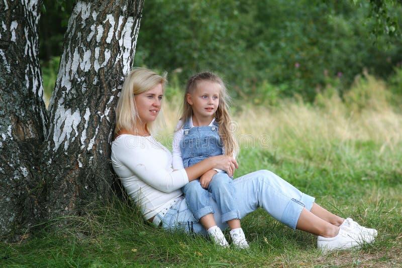 Família feliz na natureza A mãe bonita e feliz abraça delicadamente sua filha pequena com cabelo louro na perspectiva da grama imagem de stock