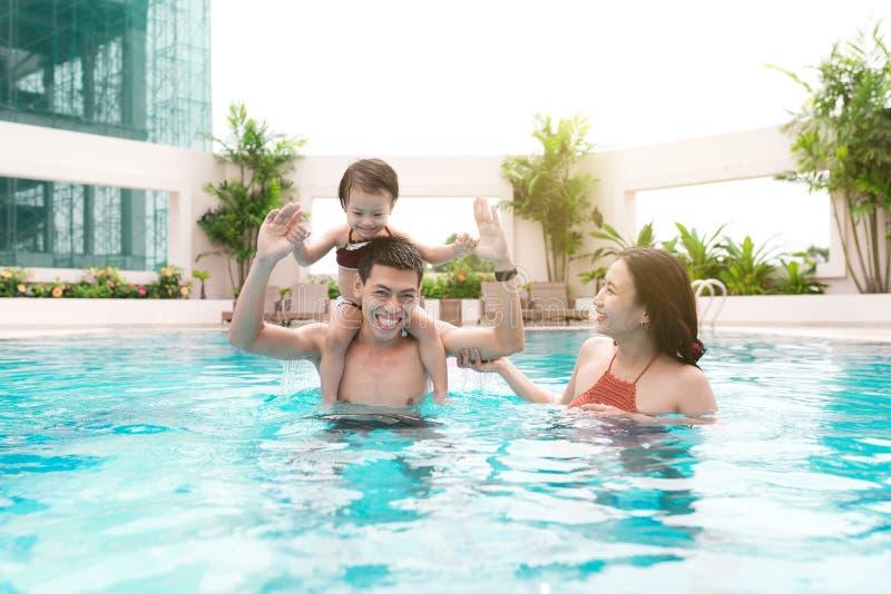 Família feliz na piscina Férias de verão e férias concentradas fotografia de stock royalty free