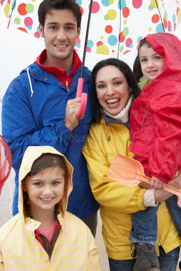 Família feliz na praia com guarda-chuva fotos de stock royalty free