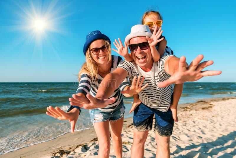 Família feliz na praia Povos que têm o divertimento em férias de verão Pai, mãe e criança contra o mar e o fundo azuis do céu fotos de stock royalty free