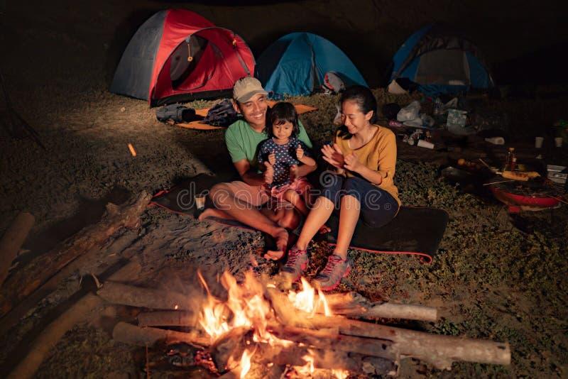 Família feliz no acampamento com fogueira fotos de stock royalty free