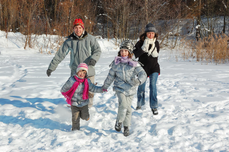 Família feliz no inverno, tendo o divertimento com neve fora imagens de stock royalty free