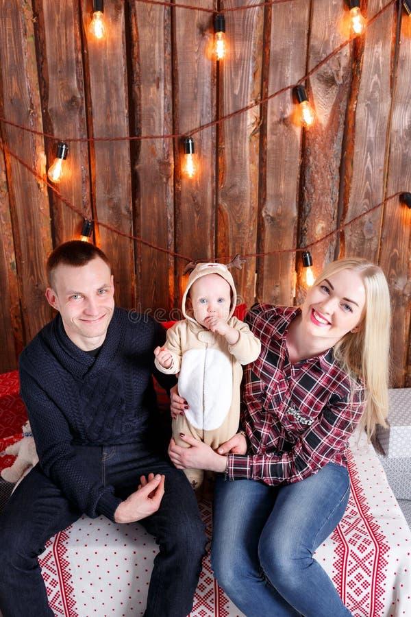 Família feliz no Natal Os pais e o assento do bebê parede de pranchas e da festão de madeira imagens de stock