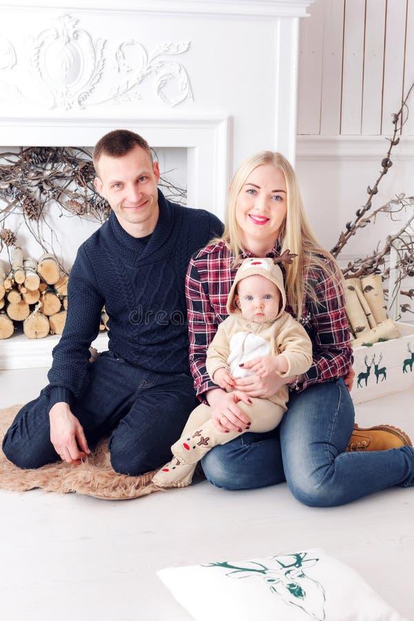 Família feliz no Natal Os pais e o bebê que encontram-se no assoalho e no sorriso imagem de stock