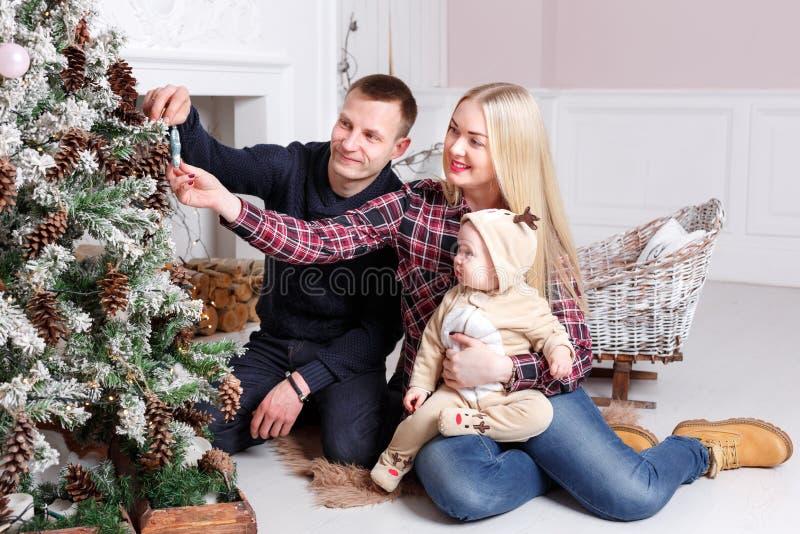 Família feliz no Natal Os pais e o bebê que sentam-se no assoalho e no sorriso fotografia de stock royalty free