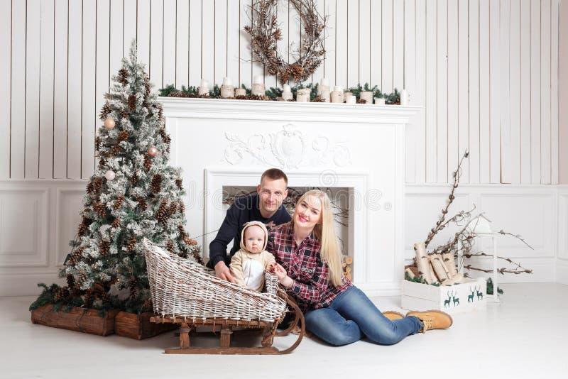 Família feliz no Natal Os pais e o bebê que sentam-se no assoalho e no sorriso foto de stock