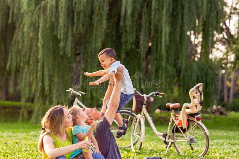 Família feliz no pai do parque do verão que aumenta seu menino acima fotos de stock royalty free