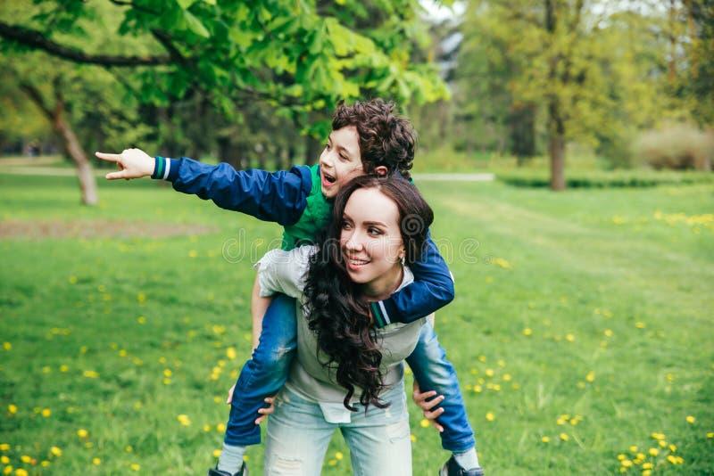 Família feliz no parque da mola mãe nova e seu filho que passam o tempo exterior em um dia de verão fotos de stock