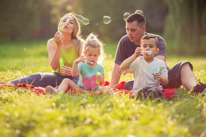 Família feliz no parque em bolhas de sabão do sopro do dia ensolarado fotografia de stock