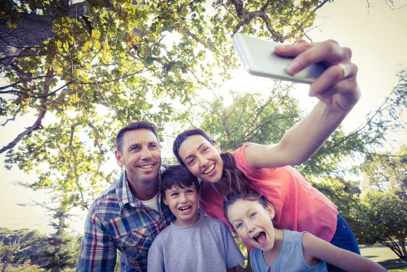 Família feliz no parque que toma o selfie fotos de stock