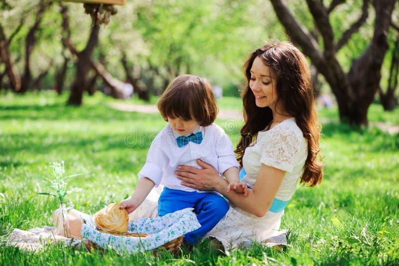 Família feliz no piquenique para o dia de mães Filho da mamã e da criança que come os doces exteriores na mola ou no verão foto de stock