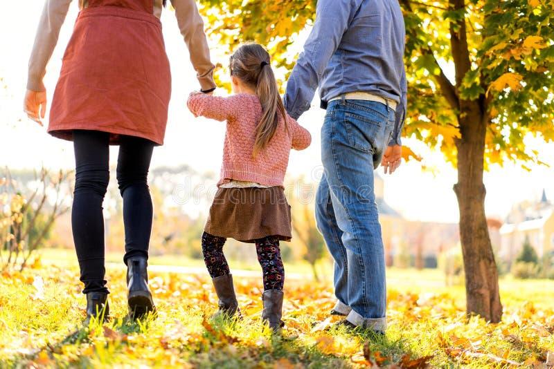 Família feliz no por do sol que anda no parque no outono foto de stock