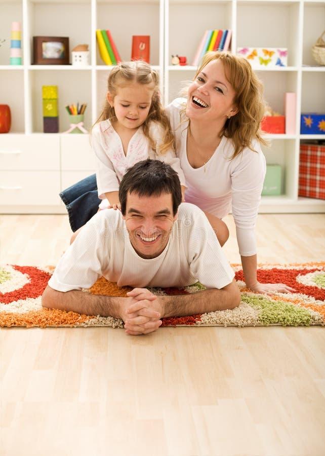 Família feliz no quarto dos miúdos imagem de stock