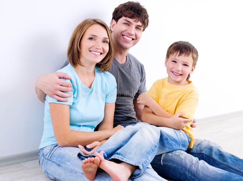 Família feliz nos casuals no assoalho fotografia de stock