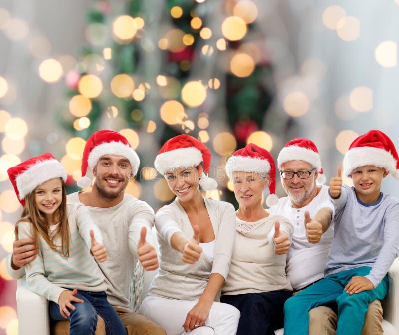 Família feliz nos chapéus de Santa que mostram os polegares acima imagem de stock