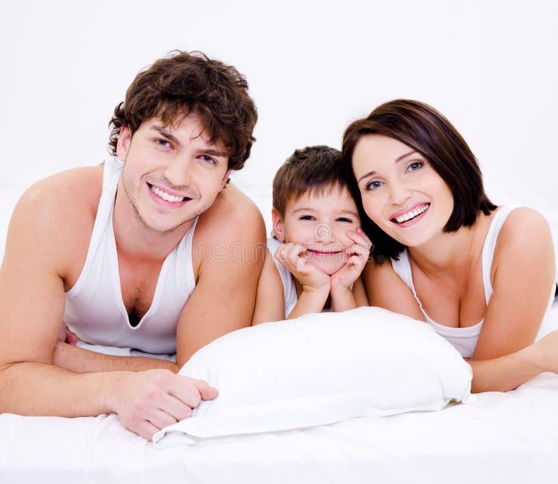Família feliz nova bonita que encontra-se na cama fotos de stock