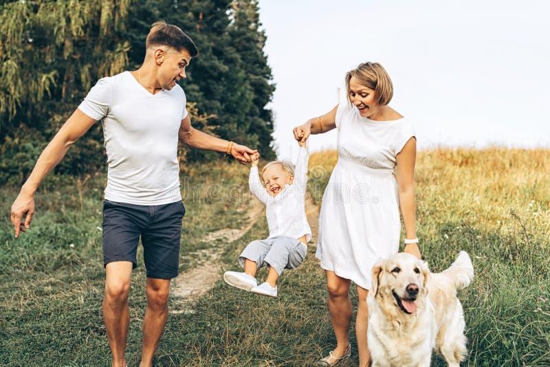 A família feliz nova com cão tem o divertimento exterior foto de stock