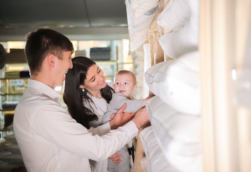 Família feliz nova na compra Casal e um bebê que anda na loja fotos de stock