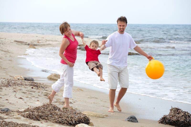 Família feliz nova na praia fotografia de stock
