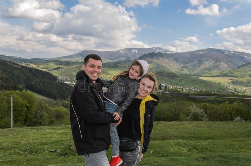 Família feliz nova: paizinho, mamã e filha durante umas férias nas montanhas foto de stock