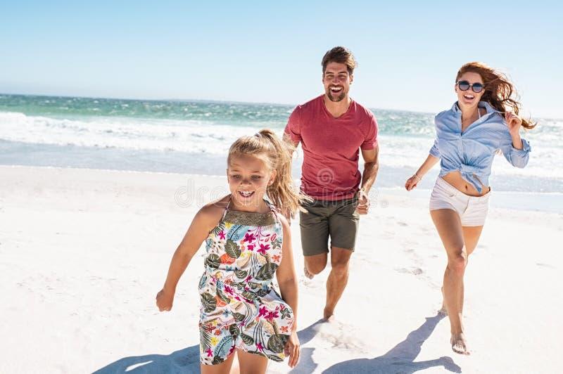Família feliz nova que corre na praia imagem de stock royalty free