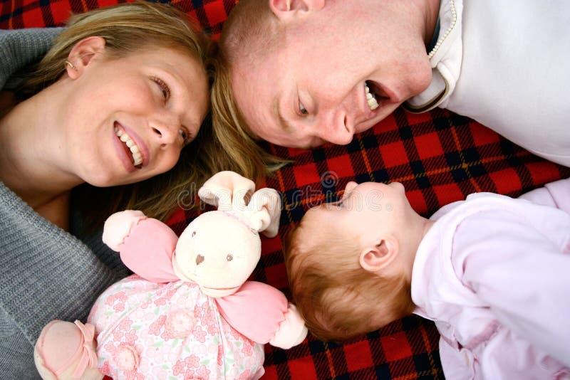 Família feliz nova que tem o divertimento ao ar livre fotos de stock royalty free