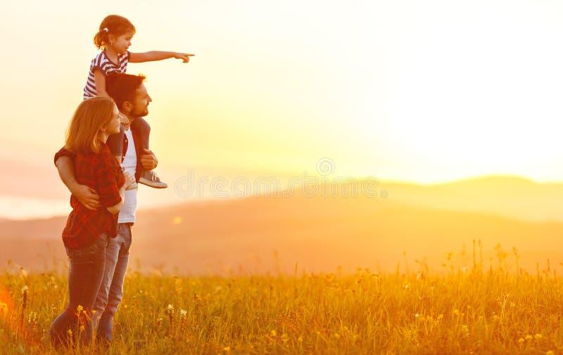 Família feliz: pai da mãe e filha da criança no por do sol imagem de stock