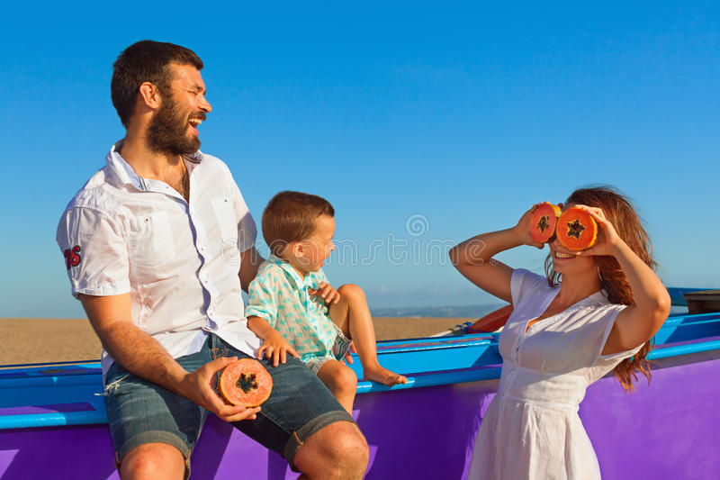 Família feliz - pai, mãe, bebê em férias da praia do verão imagem de stock