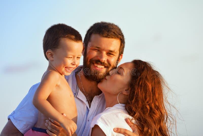 Família feliz - pai, mãe, bebê na praia do por do sol imagens de stock