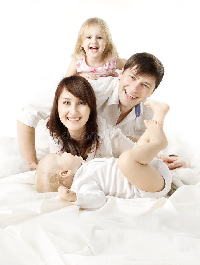 Família feliz: pais que jogam com os miúdos na cama imagens de stock royalty free
