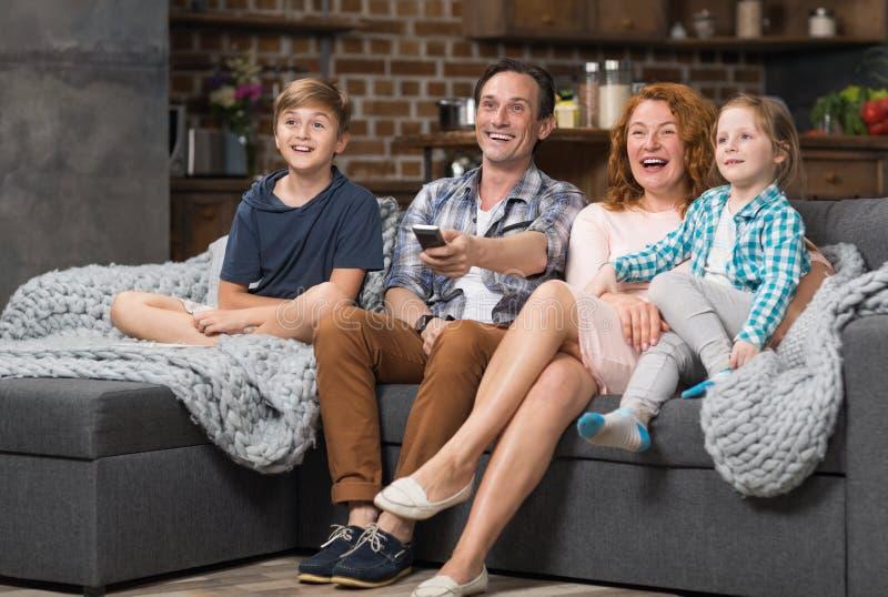 A família feliz passa junto o tempo que senta-se no sofá que olha a tevê, pais alegres com crianças imagens de stock