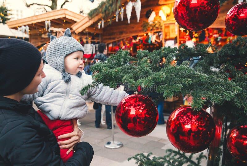 A família feliz passa o tempo em um mercado e em uma feira de rua do Natal imagens de stock