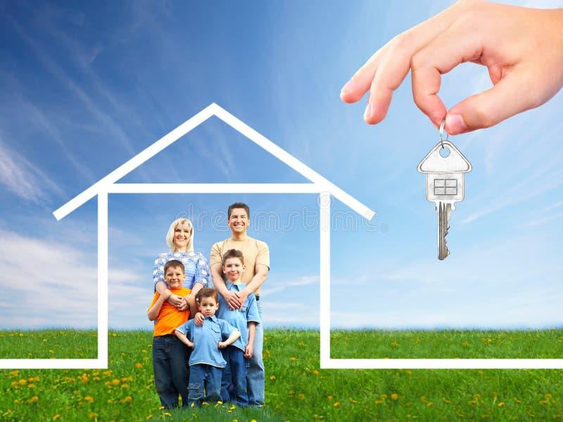 Família feliz perto da casa nova imagem de stock