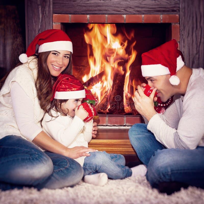 Família feliz perto da chaminé imagem de stock royalty free