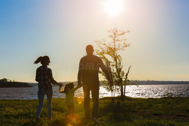 Família feliz perto do rio no dia de mola imagem de stock royalty free