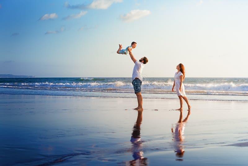 Família feliz que anda com divertimento na praia do mar do por do sol imagens de stock