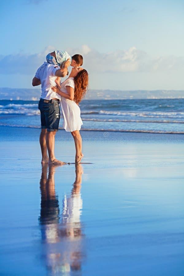 Família feliz que anda com divertimento na praia do mar do por do sol imagem de stock