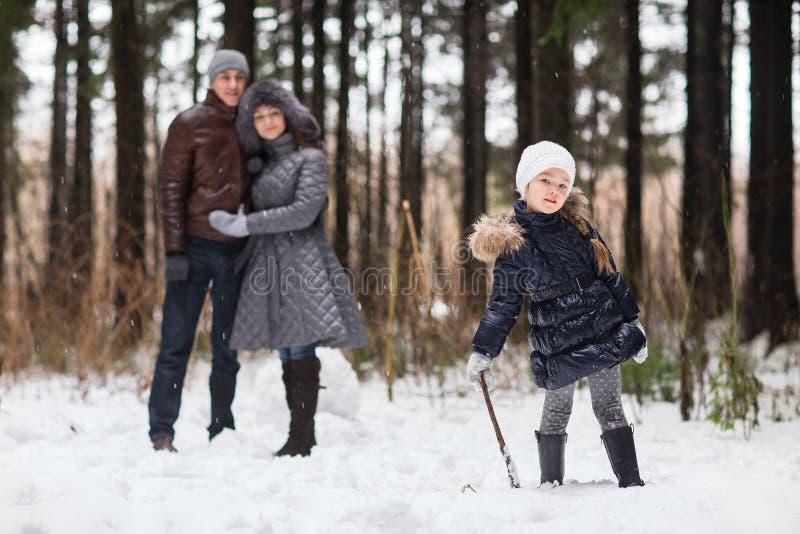 Família feliz que anda em um parque do inverno fotos de stock royalty free