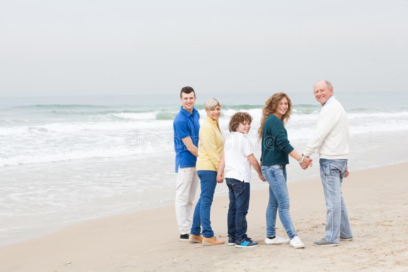 Família feliz que anda na praia foto de stock