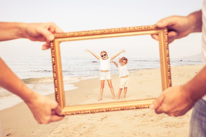 Família feliz que anda na praia no tempo do dia foto de stock royalty free