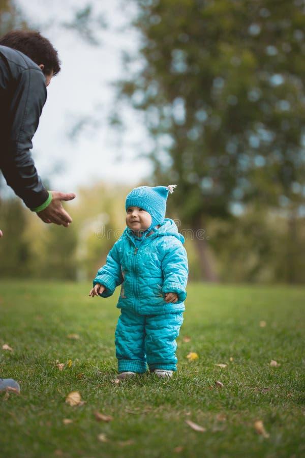 Família feliz que anda no parque do outono: pai e seu filho pequeno - aprenda dar uma volta independentemente foto de stock