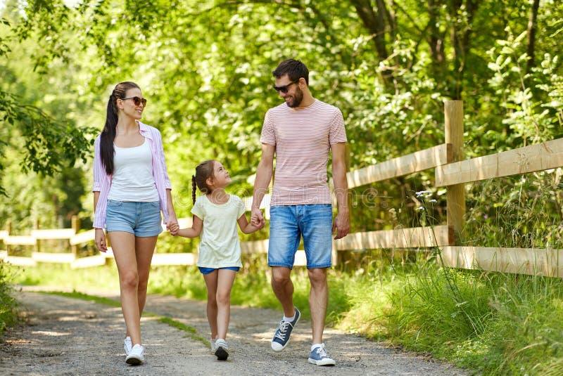 Família feliz que anda no parque do verão imagem de stock