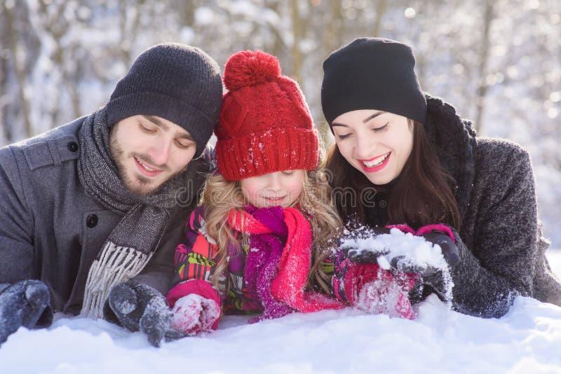 Família feliz que coloca na neve na floresta do inverno fotos de stock