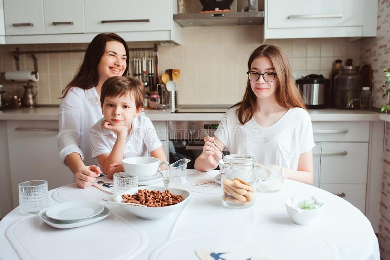 Família feliz que come o café da manhã em casa Mãe com as duas crianças que comem na manhã na cozinha branca moderna imagem de stock