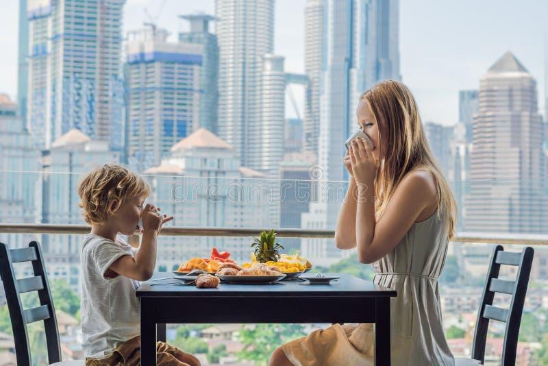 Família feliz que come o café da manhã no balcão Tabela de café da manhã com o fruto e o pão do café croisant em um balcão contra fotografia de stock