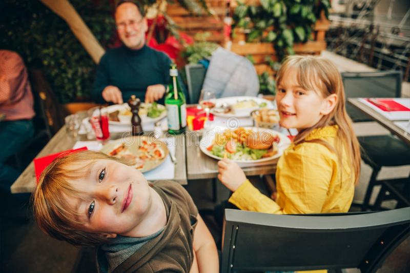 Família feliz que come o Hamburger com batatas fritas e pizza imagens de stock royalty free