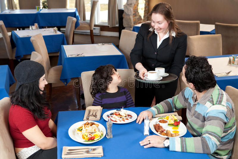 Família feliz que come o pequeno almoço em um restaurante fotos de stock royalty free